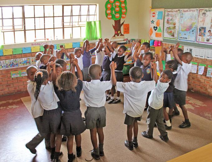 Tanzen, Bewegungsspiele und Gesang schaffen eine entspannte und fröhliche Lernatmosphäre.