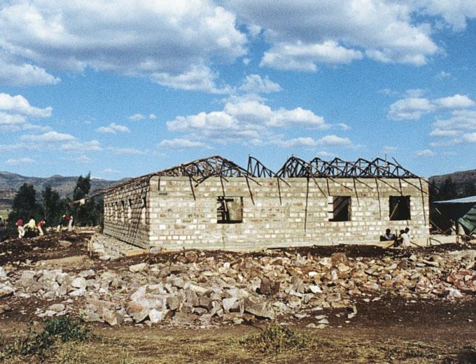 Richtfest 1993: Der Rohbau ist fertiggestellt. Blick auf die Schmalseite des L-förmigen Baukörpers.