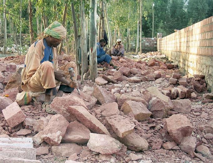 Bauarbeiten 1993: Alle Mauersteine werden zuvor aus angelieferten größeren Felsstücken mit der Hand in Form geschlagen.